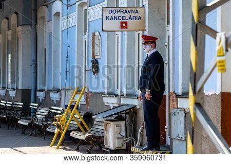 Ruzomberok, Slovakia - April 1, 2020: Steward With Face Mask And Empty Train Station