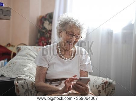 Lovely old lady using happily a smartphone.