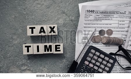 Tax-filling Concept - Tax Time Words On Wooden Blocks With The U.s Irs 1040 Form,pen,calculator,eyeg
