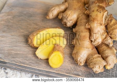 Ginger Roots And Ginger Root Sliced On Cut Board. Ginger Used As For Food And Treatment In Alternati