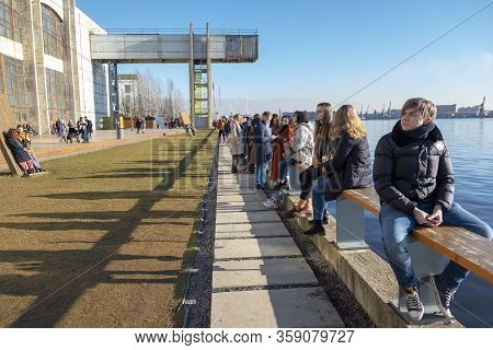 Saint Petersburg/ Russia - 09.03.2020: Men And Women Of Different Ages Are Sitting On The Parapet Of