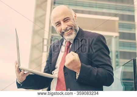 Happy Successful Mature Business Leader With Laptop Celebrating Triumph. Elderly Man In Formal Suit