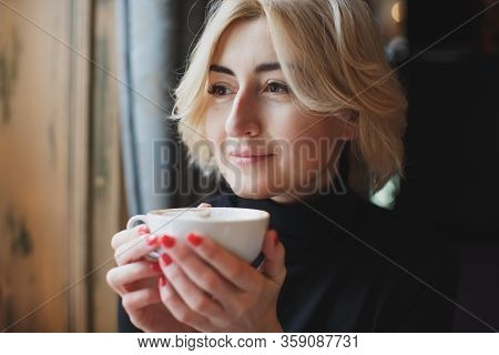 A Beautiful Woman Drinks Coffee From A White Mug.