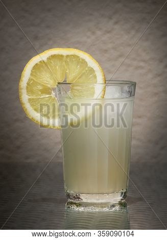 Lemon Slice And Fresh Cold Lemon Juice In The Vintage Glass Against A Low Key Background. Selective