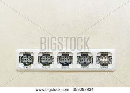 White Socket Outlets On Beige Wall Witout Cover. Copy Space. Eu Standart Electric Outlets.
