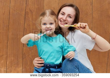 Oral Hygiene. Little Child Girl With Mother Brushing Her Teeth With A Toothbrush And Looking At The