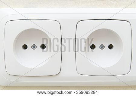 White Socket Outlets On Beige Wall. Close - Up Eu Standart Electric Outlets.