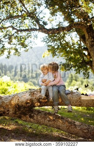 Two Grimy Sister Sitting On A Felled Tree At A Campground In The Mountains. Family Vacation Camping.