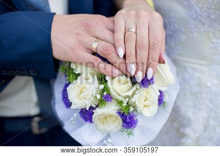 Hands And Rings On Wedding Bouquet. Wedding Theme