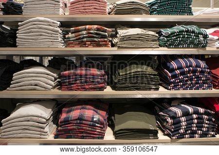Many Folded Plaid Shirts Lie On Store Shelves
