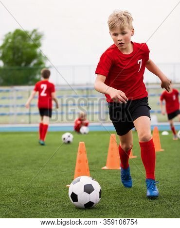 Soccer Boy On Training With Ball And Soccer Cones. Dribbling Drill. Soccer Kids Dribble Training. Yo