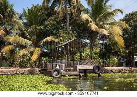 Canal Shore Of A River In The Tropics Of India, Alapuzha, Kerala. Green Shore With Palm Trees And Bu