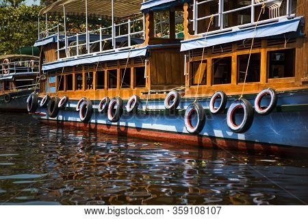 Multicolored Painted Old Car Tires Hang Over The Side Of A Pleasure Boat. Beautiful Protection Of Th