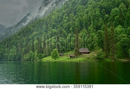 A Rustic Shelter Nestles Under Steep Forested Slopes In A Small Clearing Next To The Königssee In Ba