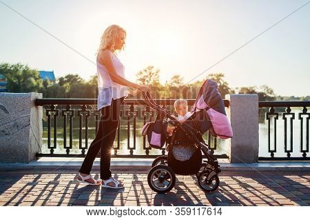 Mothers Day. Young Mother Walking In Spring Park With Infant In Baby Carriage. Woman Spends Time Wit