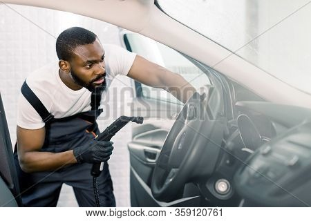Cleaning Of Car Salon With Steam Cleaner. Side View Of Professional Male African Worker Cleaning Car