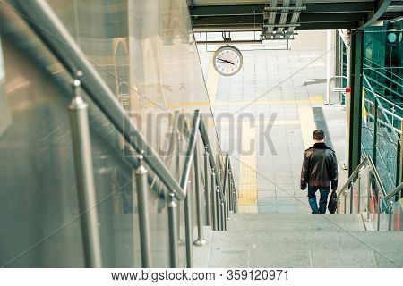 Man With Brown Leather Jacket Descending The Stairs At The Train Station.