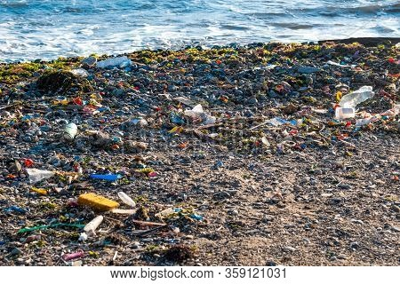 Trash Dumped On The Beach Sand. Environment And Pollution Concept.