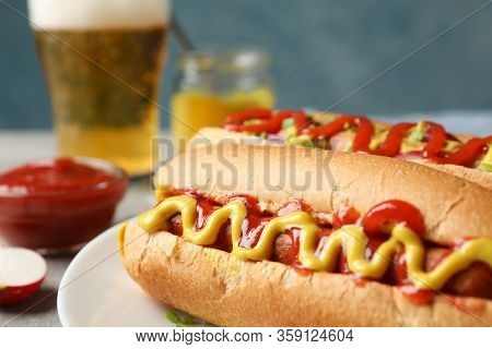 Tasty Hot Dogs, Beer And Fries Potato On Gray Table