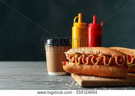 Tasty Hot Dogs, Coffee And Sauces On Wooden Background