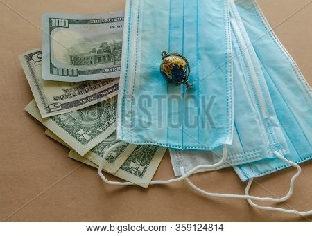 Us Paper Currency With Blue Medical Disposable Protective Masks And Small Globe On A Brown Backgroun