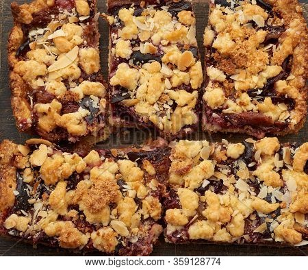 Plum Pie Crumble On A Brown Wooden Cutting Board, Top View