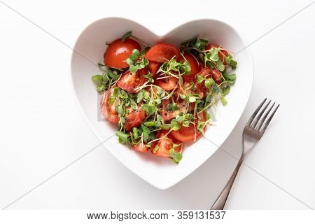 Fresh Salad With Tomato And Microgreen Radishes In Diah Shaped Of Heart Isolated On White. Top View.