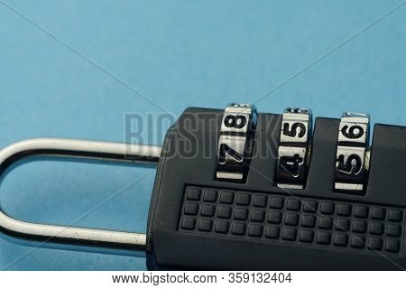Close Up Numbered Padlock Over Blue Background. Vulnerability Copy Space Concept