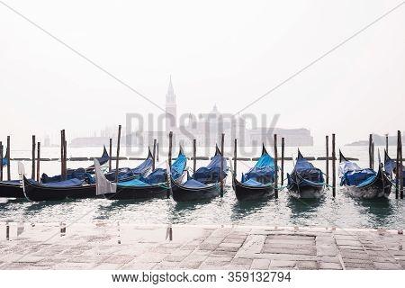 Gondolas On Grand Canal In Venice In Foggy Morning. Gondola Service For Tourist Travel Around Venice
