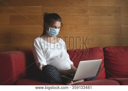 A Pregnant Young Woman Works At Home. Stay At Home. Online Education. Wearing A Face Mask.