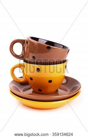 Brown And Orange Cups In Peas On Saucer, Isolate. Multicolored Cup Of Tea On Saucer On White Backgro