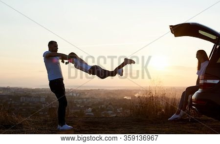 Silhouette Of A Father Swinging His Daughter By The Hands, Mother Sitting In The Car Trunk On Top Of