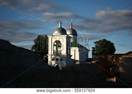 Ancient Russian City Of Izborsk. Ancient Stone Fortress. Beams Of The Evening Sun Light White Walls,
