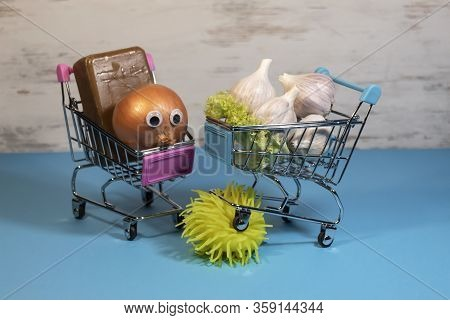 A Shopping Cart With Garlic Drove Into The Layout Of The Coronavirus Covid-19. Next To The Second Ca
