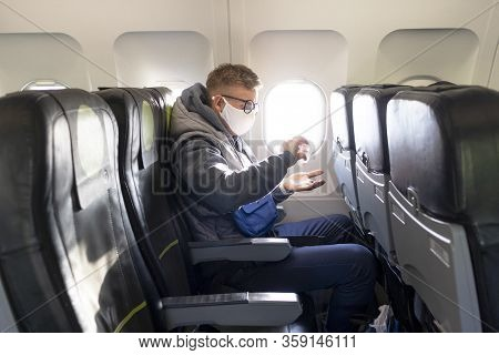 Guy In Airplane, Young Man In Glasses, Medical Protective Sterile Mask On His Face Sitting On Plane