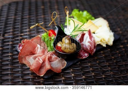 Sliced Meat And Cheese Appetizer With Pickled Olives And Lettuce Leaves. Cold Appetizers, Gourmet Lu