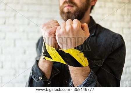 Man Hands Tied During Corona Virus Quarantine, Back And Yellow Signal Tape Marked With Covid-19 Insc