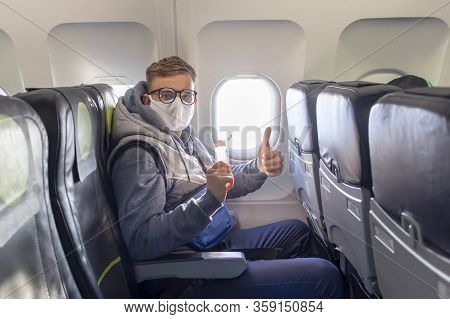 Man On Airplane Show Thumb Up In Glasses, Medical Protective Sterile Mask On His Face Sitting On Pla