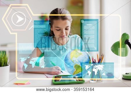 education, school and technology concept - girl with tablet pc computer and hologram projection of earth planet or globe learning geography online at home