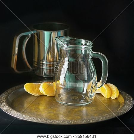 Glass Decaner And Metal Mug And Several Bright Segments Of Orange On Vintage Tray On Dark Background