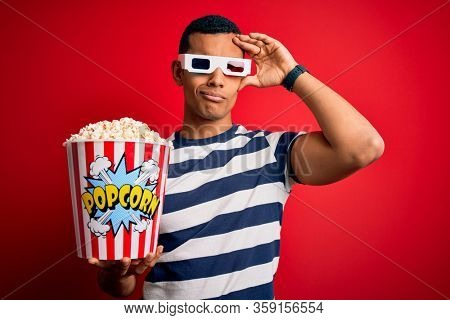 Young handsome african american man watching movie using 3d glasses eating popcorns worried and stressed about a problem with hand on forehead, nervous and anxious for crisis