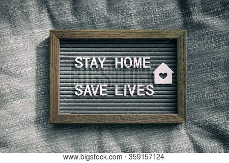 COVID-19 text for self isolation staying at home . Stay home, save lives. Coronavirus quote sboard sign with message of self quarantine for social responsability on home background.
