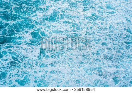 Texture Light Blue Surface Of Raging Sea Water With White Foam And Wave Pattern.the Azure Surface Of