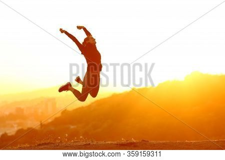 Silhouette Of An Excited Runner Woman Jumping At Sunset In City Outskirts