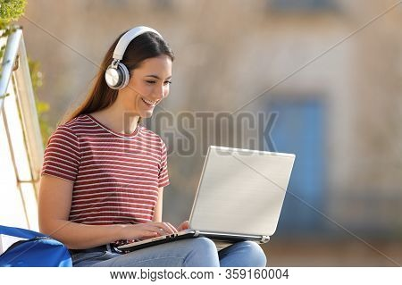 Happy Student E Learning Wearing Headphones And Using A Laptop Sitting Outdoors In A University Camp