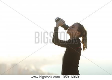 Profile Of A Runner Hydrating Drinking Water From Plastic Bottle After Exercise Outdoors