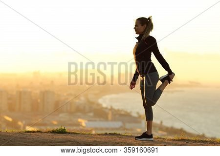 Runner Stretching Leg In City Outskirts