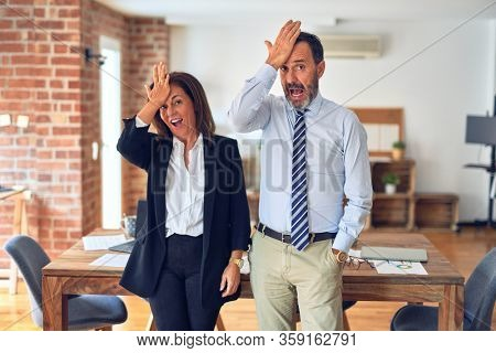 Two middle age business workers standing working together in a meeting at the office surprised with hand on head for mistake, remember error. Forgot, bad memory concept.