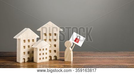 Residential Buildings And Man Holding Red Padlock Sign. Tough Measures To Stop New Infections Of Cor