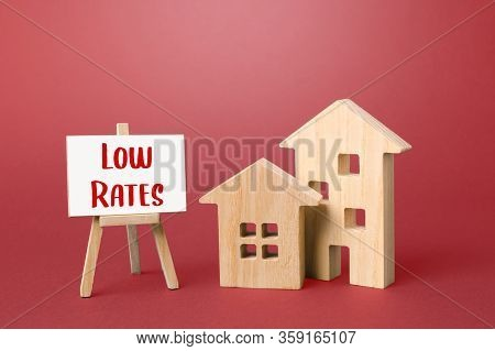 Figurines Of Houses And An Low Rates Easel. Big Promotions And Discounts On Home Sales. Low Demand F